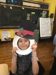 second grader with paper snowman hat
