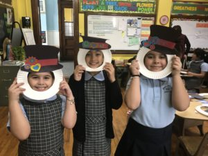 second graders with paper snowman hat